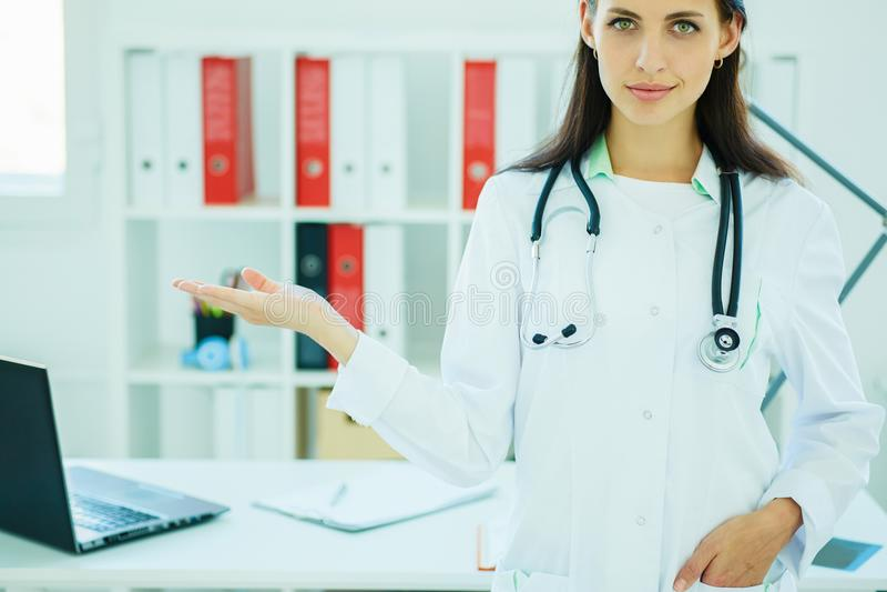 Счастливый молодой красивый женский доктор показывая пустую зону для знака или copyspace стоковое изображение rf