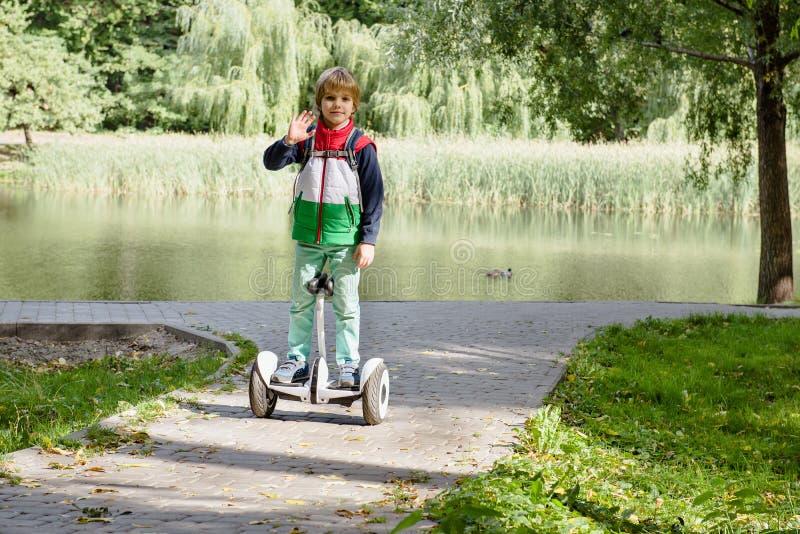 Счастливый молодой мальчик балансируя на электрическом hoverboard стоковые фотографии rf