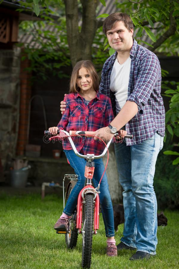 Счастливый молодой отец с маленьким велосипедом катания дочери на траве стоковое фото rf