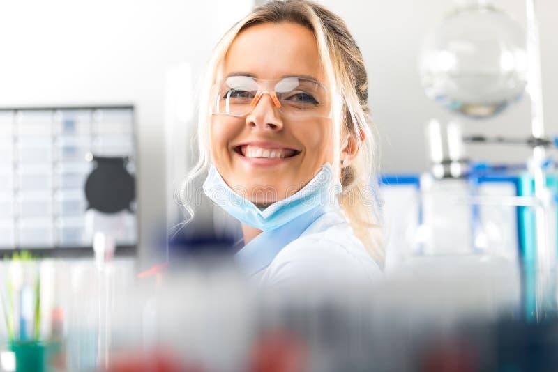 Счастливый молодой привлекательный усмехаясь ученый женщины в лаборатории стоковые фото