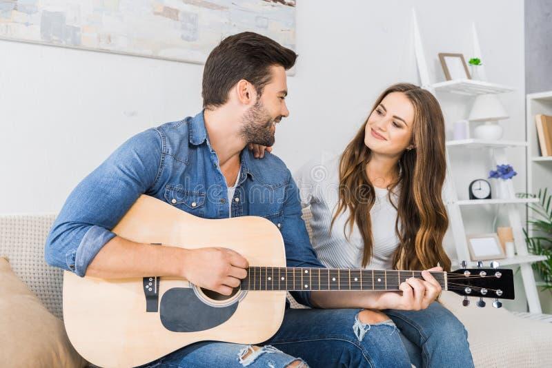 счастливый молодой человек играя на акустической гитаре и смотря его девушку стоковые фотографии rf