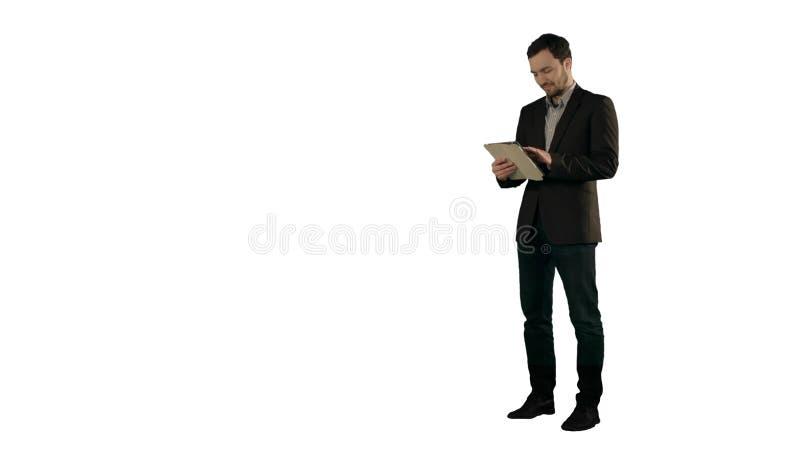 Счастливый молодой человек используя таблетку цифров на белой изолированной предпосылке стоковые изображения