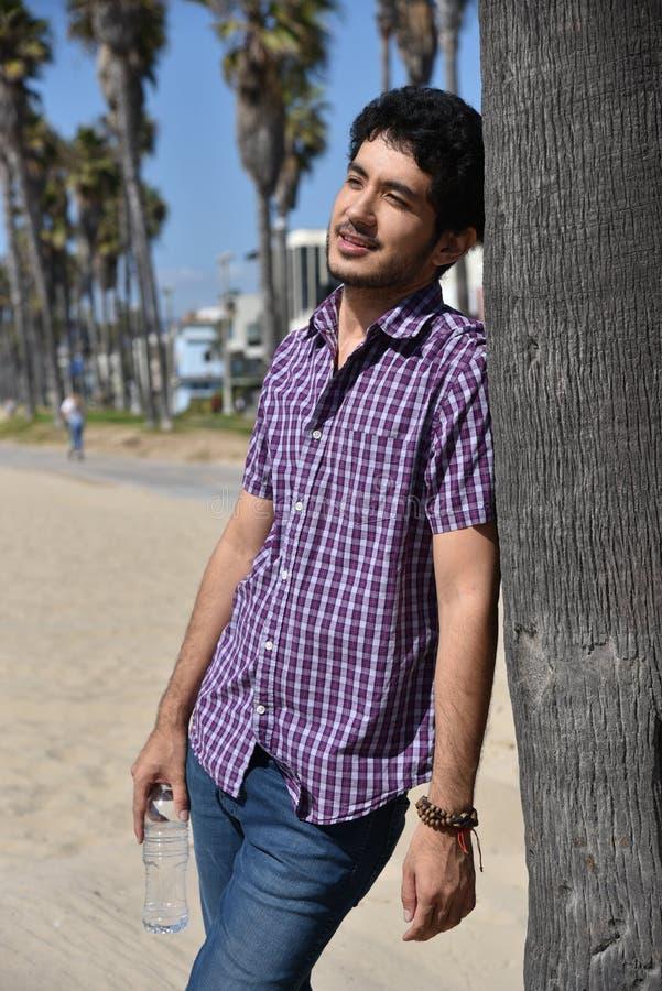 Счастливый молодой человек на каникулах на пляже стоковая фотография