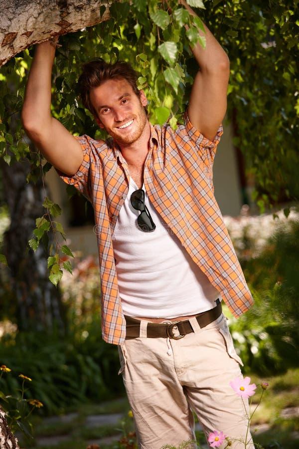 Счастливый молодой человек представляя валом стоковое фото