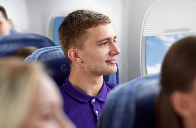 Счастливый молодой человек путешествуя самолетом стоковые фото