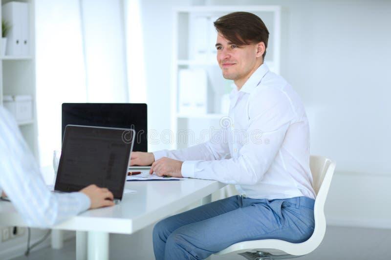 Счастливый молодой человек работает на его компьтер-книжке в офисе стоковое изображение