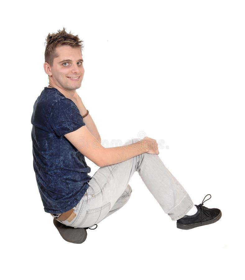 Счастливый молодой человек сидя на поле стоковое фото rf