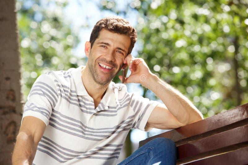 Счастливый молодой человек сидя outdoors и говоря на сотовом телефоне стоковые фото