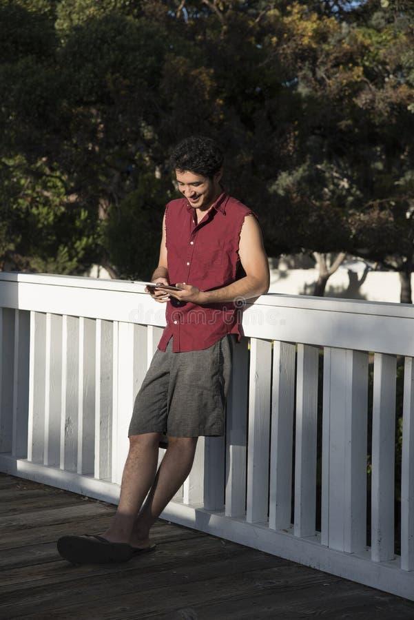 Счастливый молодой человек с компьютером экрана касания стоковая фотография