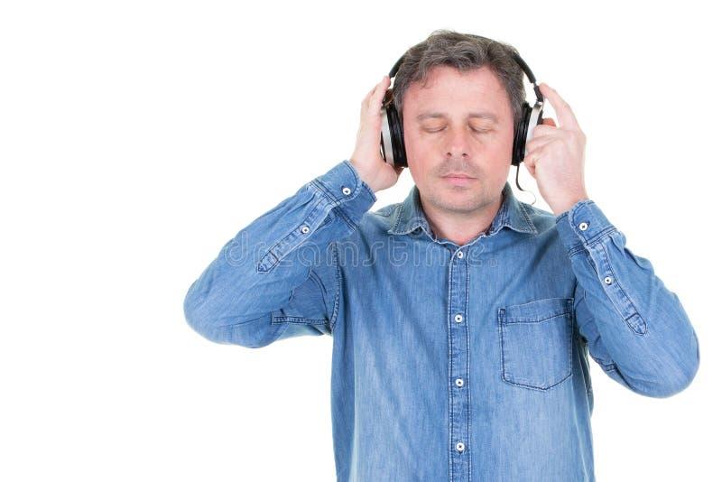 Счастливый молодой человек с наушниками закрыл музыку глаз слушая стоковое изображение