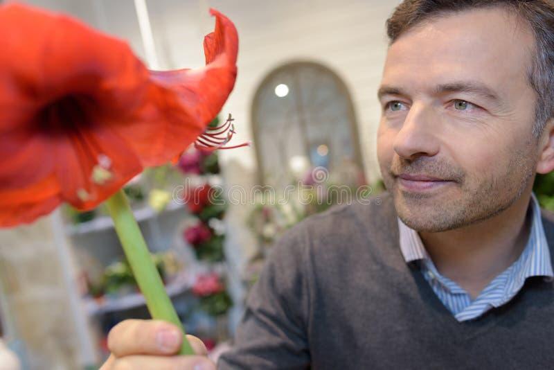 Счастливый мужской клиент держа цветковые растения в магазине стоковое фото