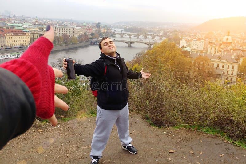 Счастливый мужской турист предлагает консервную банку пива к другу на фоне панорамы чехословакской столицы Праги стоковое изображение