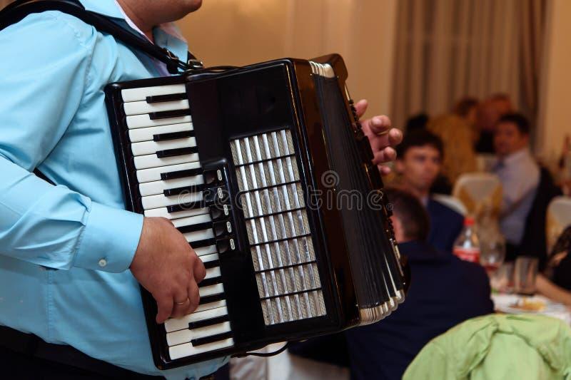 Счастливый музыкант аккордеона играя на приеме по случаю бракосочетания, руке на h стоковое фото rf
