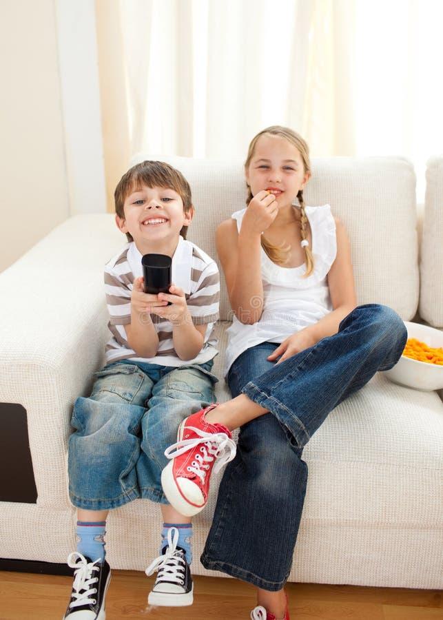 счастливый наблюдать tv отпрысков стоковые изображения rf