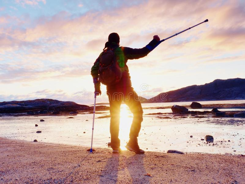 Счастливый неработающий человек на пляже держа его предплечье crutches над головой, теплым заходом солнца стоковая фотография rf