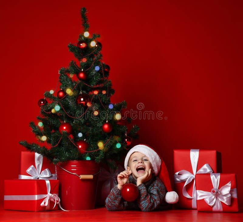 счастливый новый год xmas Портрет ребенка в подарках рождества красной шляпы Санта ждать стоковые фото