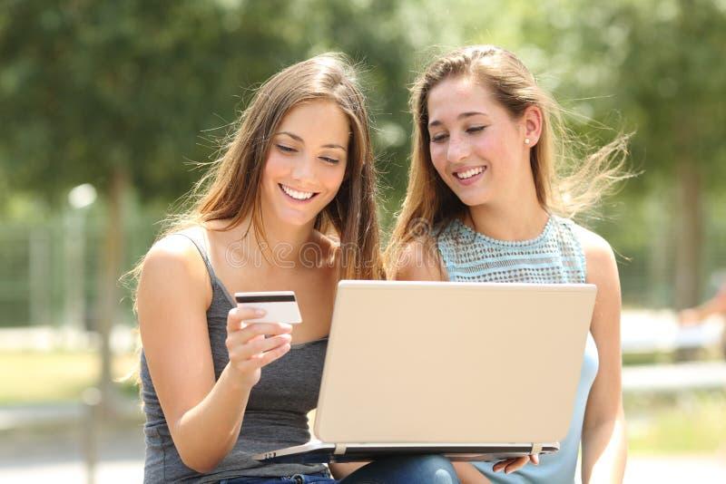 Счастливый оплачивать друзей онлайн с кредитной карточкой в парке стоковая фотография