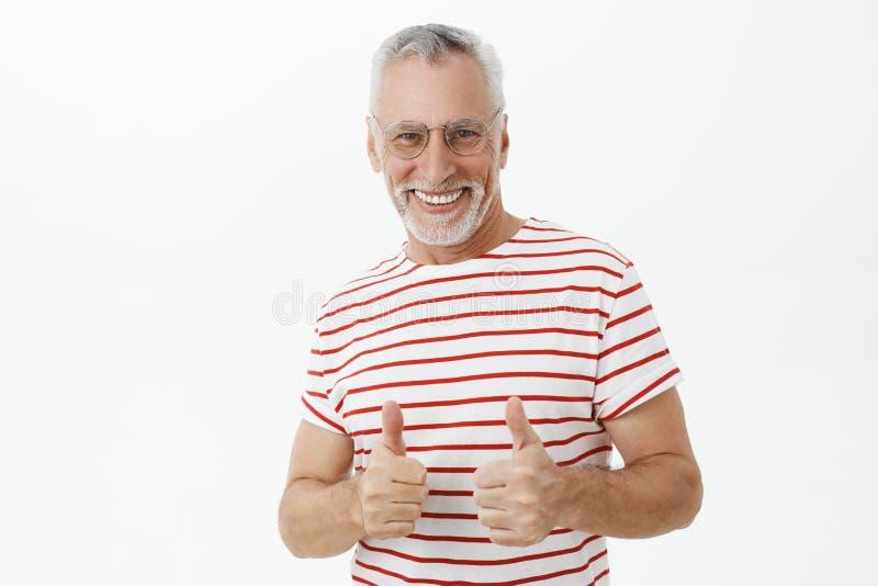 Счастливый оптимистический и подпитанный харизматический старик с бородой в стеклах и striped футболке показывая большие пальцы р стоковое изображение