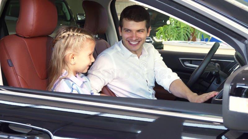 Счастливый отец говорит его дочь о функции автомобиля стоковая фотография