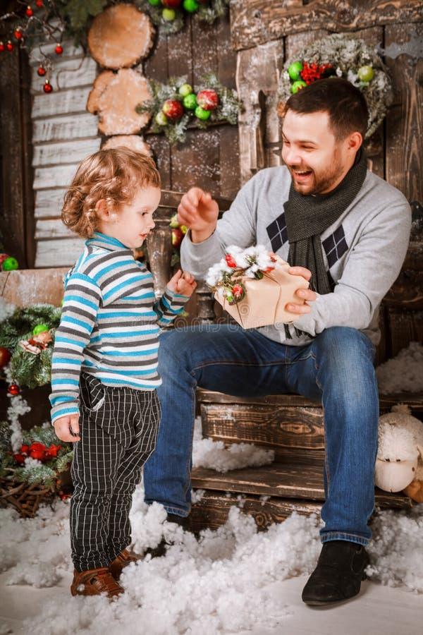 Счастливый отец дает подарок рождества к его сыну в украшениях с елью с подарочными коробками и деревянной предпосылкой стоковое фото rf