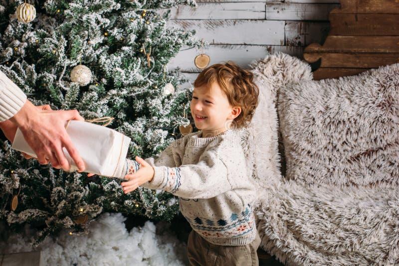 Счастливый отец дает подарок рождества к его сыну в украшениях с елью с подарочными коробками и деревянной предпосылкой мило стоковое изображение rf