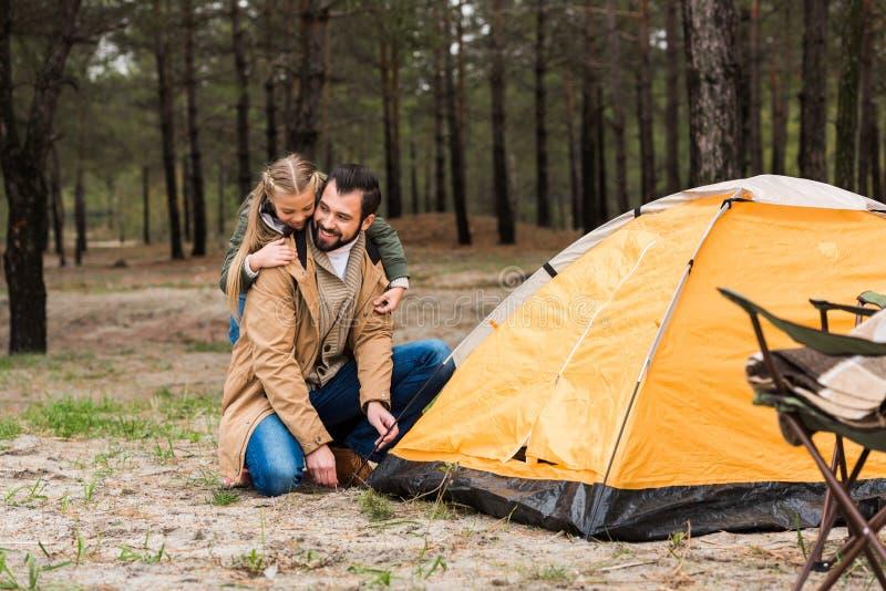 счастливый отец и дочь устанавливая шатер стоковая фотография rf
