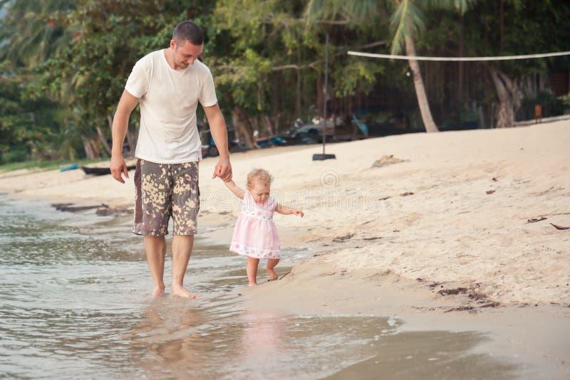 Счастливый отец и малая дочь идя вместе с держать руки на пляже стоковые изображения