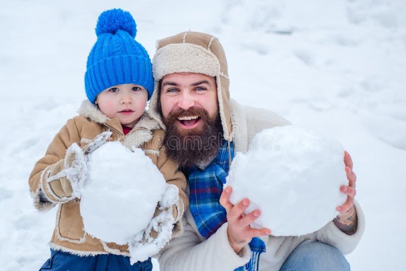 Счастливый отец и сын делая снеговик в снеге Handmade смешной человек снега Отец и сын делая снежный ком на белизне зимы стоковое фото rf