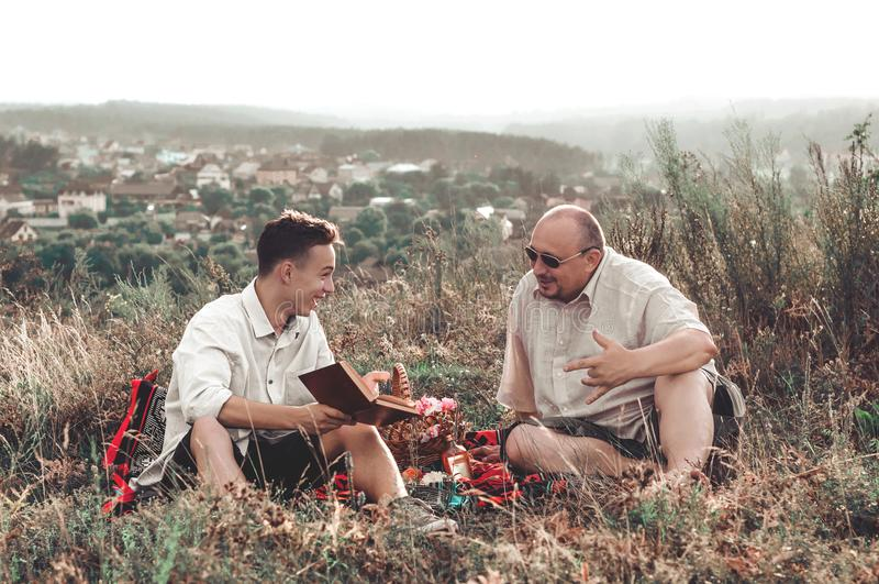 Счастливый отец и сын имея остатки на природе на летний день стоковое фото rf