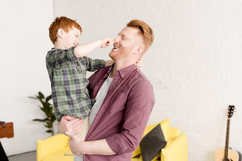 Счастливый отец и сын имея потеху совместно стоковое фото
