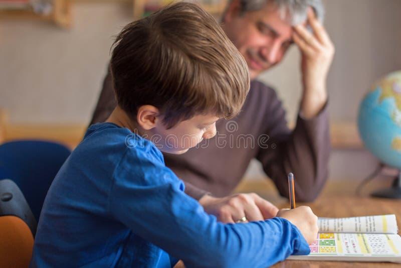 Счастливый отец и сын сотрудничая на домашней работе математики стоковые фотографии rf