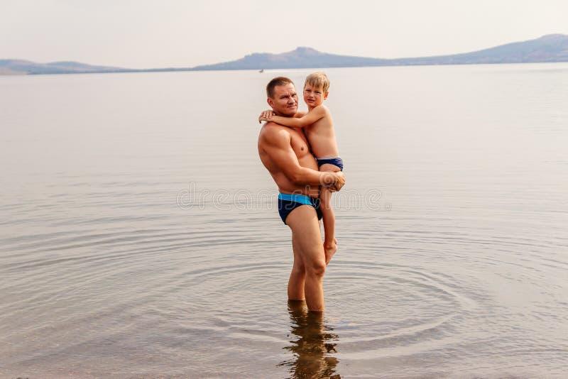 Счастливый отец обнимает его маленького сына пока стоящ в озере стоковые изображения rf