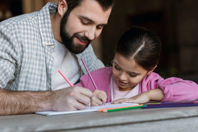 счастливый отец при маленькая дочь сидя на таблице и рисуя в scrapbook стоковое изображение rf