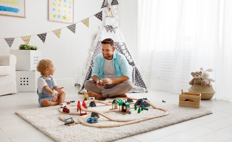 Счастливый отец семьи и сын ребенка играя в железной дороге игрушки в pl стоковая фотография