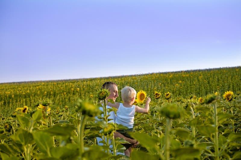 Счастливый отец с его маленьким сыном в его оружиях стоя на зеленом поле солнцецветов против голубого неба стоковая фотография