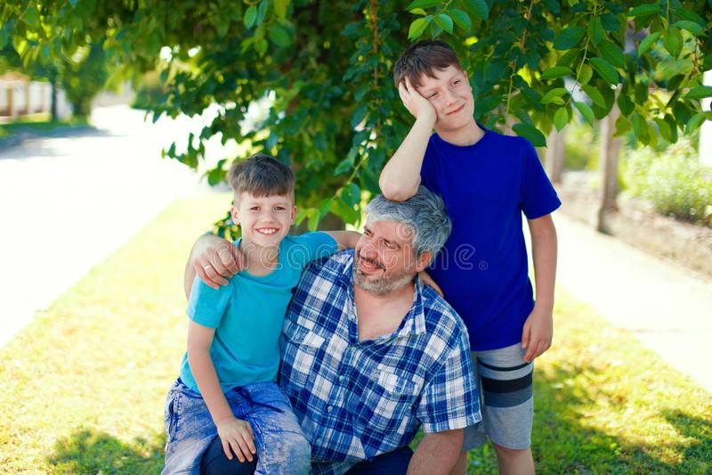 Счастливый отец с 2 молодыми сыновььями под деревом стоковая фотография rf