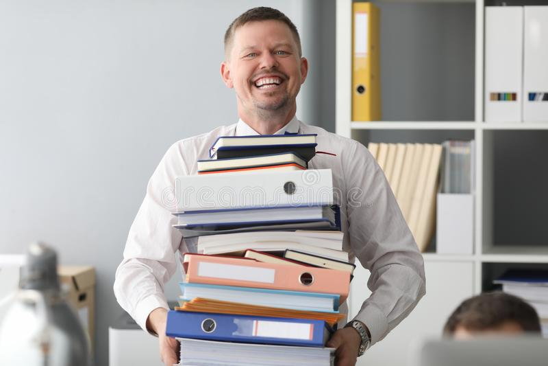 Счастливый офисный работник несет с собой огромную кучу бумаги стоковые фотографии rf