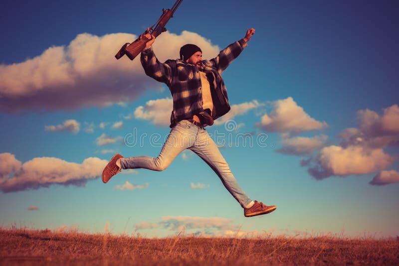 Счастливый охотник Охотник с оружием корокоствольного оружия на охоте стоковые изображения