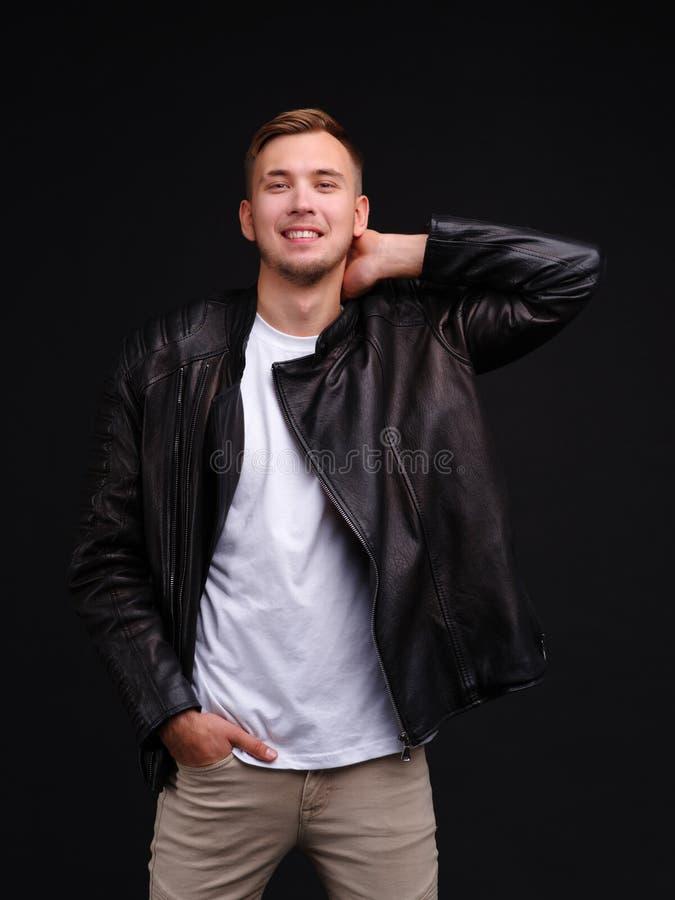 Счастливый парень в черной куртке держит к шеи с улыбкой стоковая фотография rf