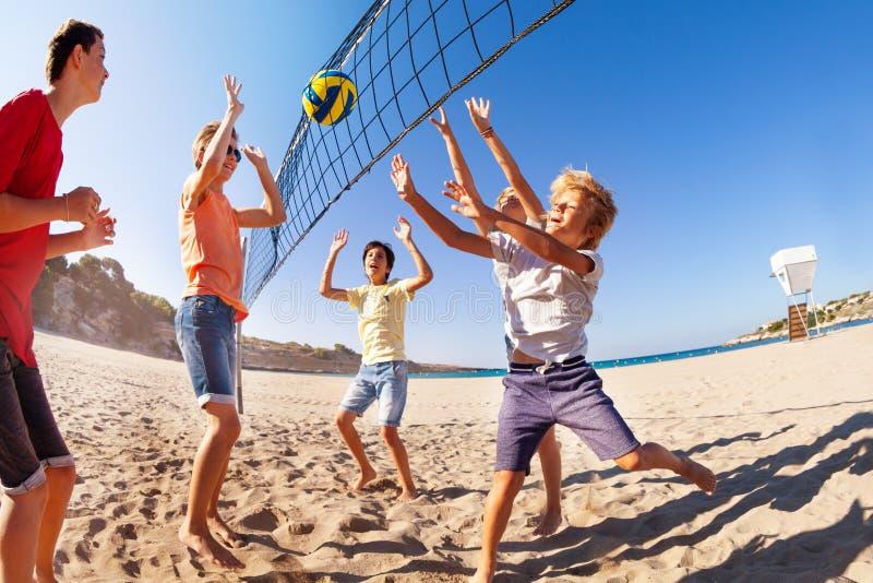 Счастливый подросток играя волейбол пляжа в лете стоковая фотография rf