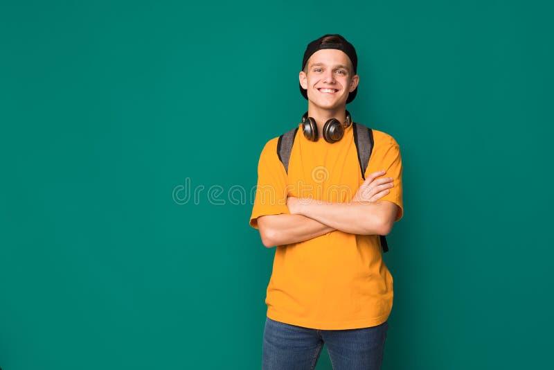 Счастливый подросток с пересеченными оружиями над предпосылкой бирюзы стоковые изображения rf