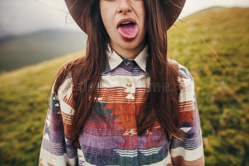 Счастливый показ девушки битника путешественника покрасил голубой язык от ест стоковое изображение rf