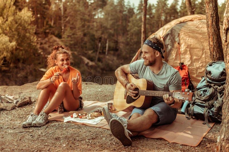Счастливый положительный человек держа музыкальный инструмент стоковое фото rf