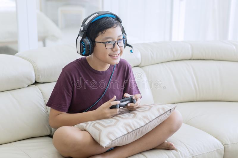 Счастливый предназначенный для подростков мальчик играя видеоигры с кнюппелем стоковое изображение