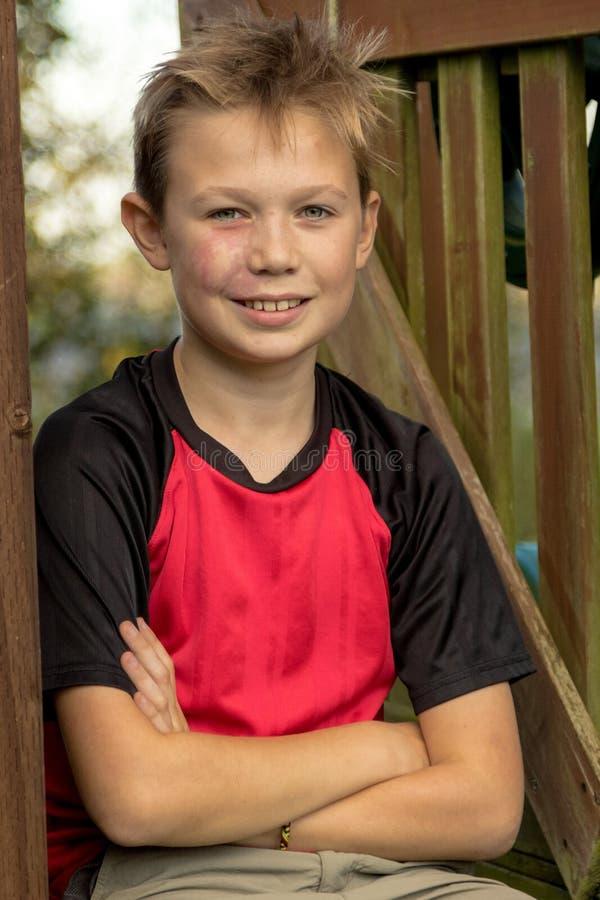 Счастливый пре-предназначенный для подростков мальчик сидя снаружи стоковая фотография rf