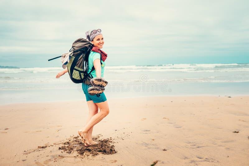 Счастливый путешественник backpacker девушки бежит barefoot на океане b песка стоковая фотография