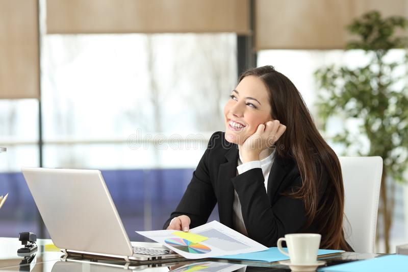 Счастливый работник офиса мечтая смотрящ сторону стоковая фотография rf