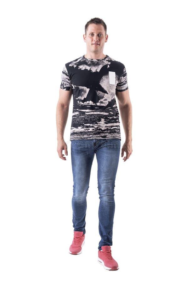 Счастливый расслабленный молодой взрослый случайный человек в джинсах причаливая и усмехаясь к камере стоковые изображения rf