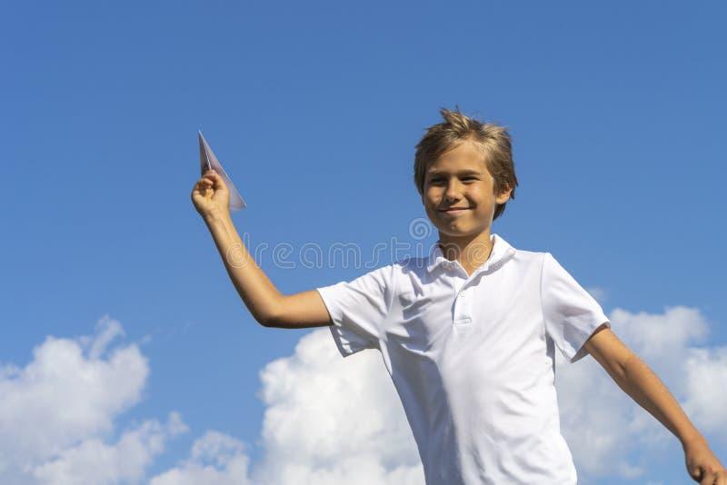 Счастливый ребенк играя с бумажным самолетом против голубой предпосылки неба лета стоковое фото