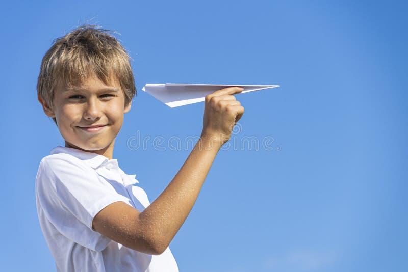 Счастливый ребенк играя с бумажным самолетом против голубой предпосылки неба лета стоковые изображения
